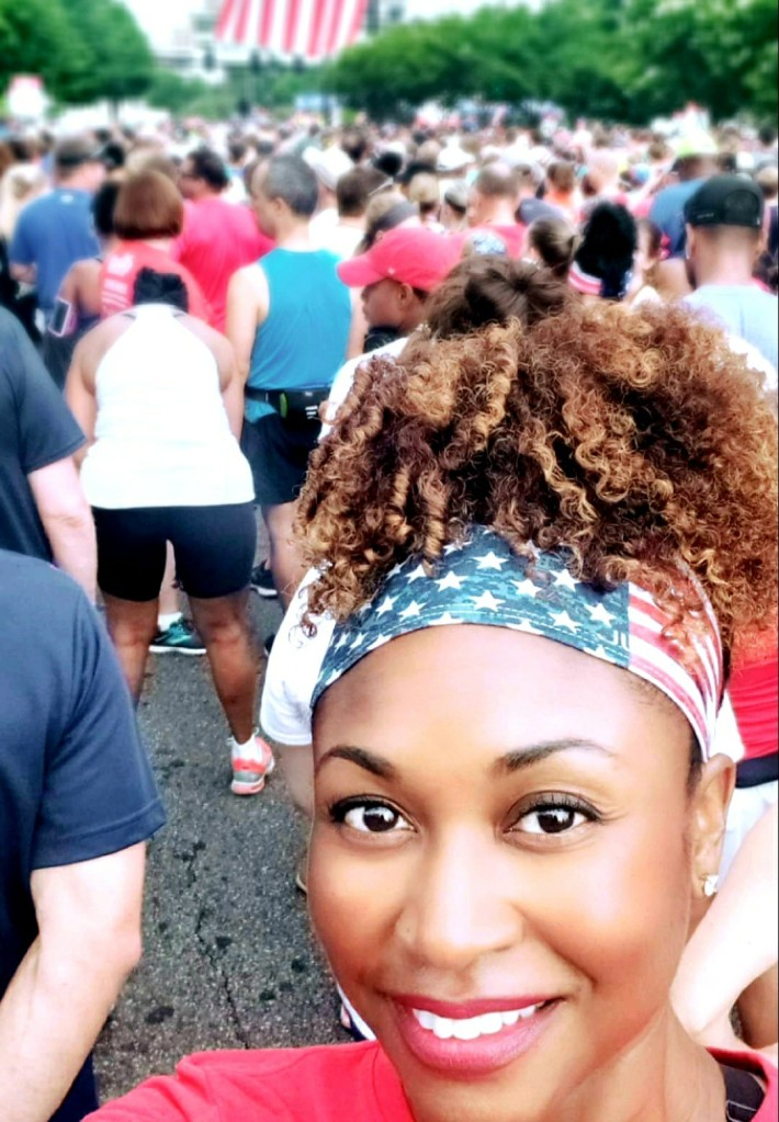 African American woman running the AJC Peachtree Road Race wearing the JUNK Honor Workout Headband